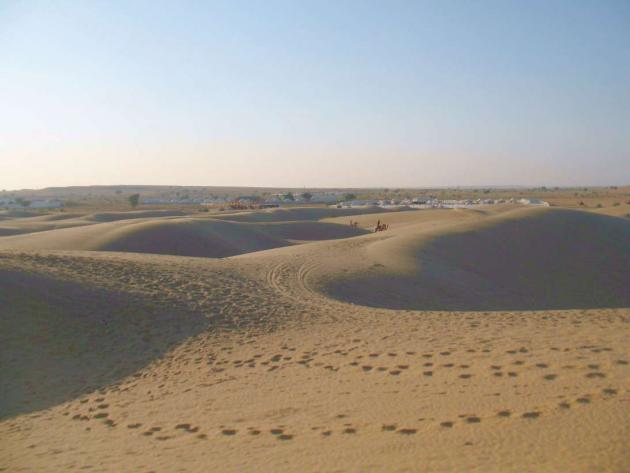 Sand dunes with white tents in the background